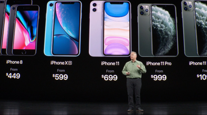 a man gives a public talk in front of a board displaying various models of iPhones, from the iPhone8 to the iPhone11, with their respective prices