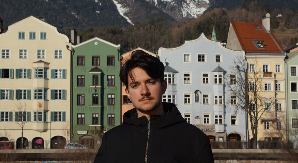 game designer Dimitrii Gruzdev of gaijin entertainment stands in front of a row of colourful houses.