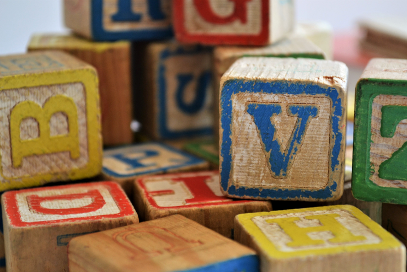 Coloured wooden alphabet blocks are stacked randomly displaying individual letters